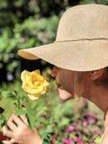 Woman Wearing Sun Hat Smelling Yellow Rose Royalty Free Stock Image