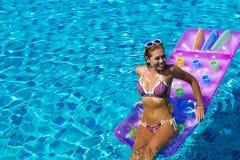 Woman wearing sunglasses and bikini poses swimming on mattress in pool. Phuket island, Thailand Stock Image