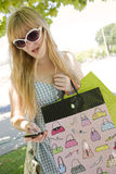 Woman wearing sunglasses. Blonde woman wearing sunglasses with shopping bags and mobile phone Stock Image