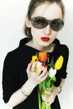 Woman wearing sunglasses with bouquet of tulips Stock Photo