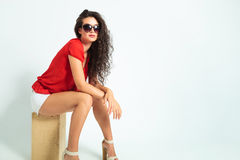 Woman wearing sunglasses and heels while sitting with hands cros Stock Images