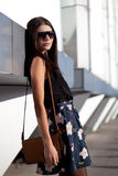 Woman wearing sunglasses with leather bag Royalty Free Stock Photos