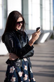 Woman wearing sunglasses looking at phone Royalty Free Stock Images