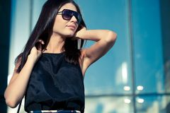 Woman wearing sunglasses over glass wall Royalty Free Stock Photography