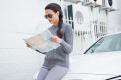 Woman wearing sunglasses reading map beside her car Stock Image