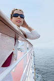 Woman wearing sunglasses stands on board of ship royalty free stock photos