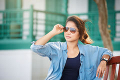 Woman wearing sunglasses,  wearing jeans and a denim jacket. She Stock Images