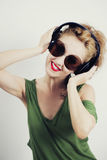 Woman wearing sunglasses and wireless headphones Stock Images
