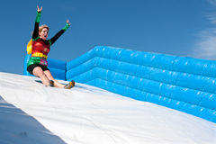 Woman Wearing Superhero Costume Goes Down Obstacle Race Slide Royalty Free Stock Photo