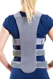 Woman Wearing Supportive Back Brace in Studio. Close Up Rear View of Blond Woman in Blue T-Shirt Wearing Padded Back Brace in Studio with White Background Stock Images