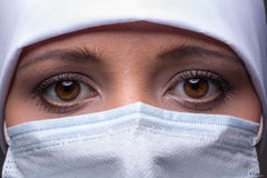 Woman wearing surgical cap and mask Stock Image