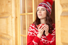 Woman wearing a sweater and hat holding cup of warm drink Stock Image