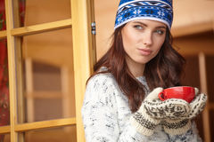 Woman wearing a sweater and white hat holding tea cup Royalty Free Stock Photography