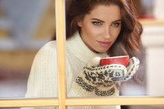 Woman wearing a sweater and white hat holding tea cup Royalty Free Stock Photos