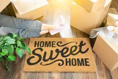 Woman Wearing Sweats Relaxing Near Home Sweet Home Welcome Mat. Moving Boxes and Plant Stock Photography