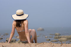 Woman wearing swimming suit with straw hat half sitting on sand sun bathing and looking to the sea in fog. Stock Photos