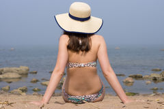 A woman wearing swimming suit and straw hat turned with a back, sitting on sand and looking to sea in fog. Stock Photography