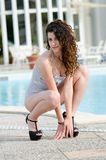 Woman wearing swimsuit and high heels sits on her legs Stock Images