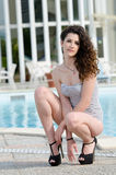 Woman wearing swimsuit and high heels sits on her legs Royalty Free Stock Photos