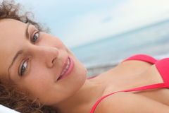 Woman wearing swimsuit is laying near water royalty free stock image