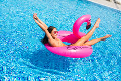Beautiful woman, wearing swimsuit, lying on a pink flamingo air mattress in a pool of blue water, summer. Woman, wearing swimsuit, lying on a pink flamingo air stock photography