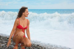 Woman wearing swimsuit is sitting near water stock images