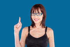 Woman wearing a tank top and eyeglasses. Woman wearing a tank top and blue eyeglasses with index finger pointing up on a blue background Royalty Free Stock Images