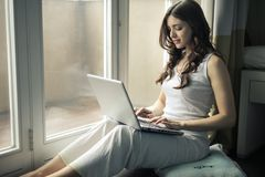 Woman Wearing Tank Top Sitting by the Window Royalty Free Stock Photos