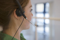 Woman wearing telephone headset on ear, side view, close-up (differential focus) Stock Photos