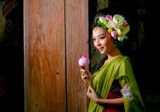 Woman wearing Thai traditional dress hand holding lotus fl royalty free stock photo