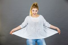 Woman wearing too big jumper. Not fitting after weight loss. Grey background Royalty Free Stock Photos