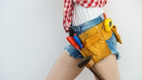Woman wearing toolbelt. Woman wearing protective workwear toolbelt on jeans shorts. Girl working at flat remodeling. Building, repair and renovation stock image