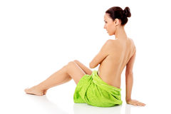 Woman wearing towel sitting on the floor, back view. Stock Photo