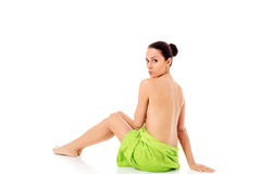 Woman wearing towel sitting on the floor, back view. Royalty Free Stock Images