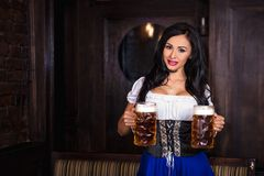 Oktoberfest woman wearing a traditional Bavarian dress dirndl posing with a beer mug at bar. Woman wearing a traditional Bavarian dress dirndl posing with a beer stock image
