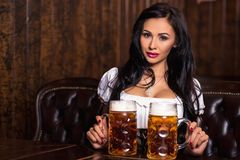 Oktoberfest woman wearing a traditional Bavarian dress dirndl posing with a beer mugs at bar Royalty Free Stock Image