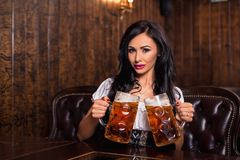 Oktoberfest woman wearing a traditional Bavarian dress dirndl posing with a beer mugs at bar. Woman wearing a traditional Bavarian dress dirndl posing with a royalty free stock photo
