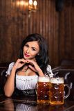 Oktoberfest woman wearing a traditional Bavarian dress dirndl posing with a beer mugs at bar. Woman wearing a traditional Bavarian dress dirndl posing with a stock photo