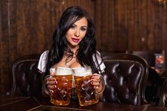 Oktoberfest woman wearing a traditional Bavarian dress dirndl posing with a beer mugs at bar Stock Photo