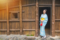 Woman wearing traditional clothing kimono. In front of old wooden house outside. Japaneses sightseeing antique japan architecture, Asian women traveling on Royalty Free Stock Photography