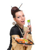 Woman wearing a traditional dress eating sushi Royalty Free Stock Images