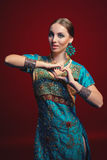 Woman wearing traditional Indian sari. With accessories- earrings, bracelets and rings and mehndi henna tattoos gesturing heart shape with hands royalty free stock photo