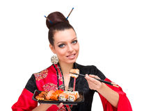Woman wearing a traditional red dress eating sushi Royalty Free Stock Photography