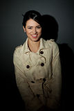 Woman wearing a trench coat and smiling Stock Images