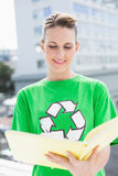 Woman wearing tshirt with recycling symbol holding notebook Royalty Free Stock Photos