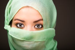 Woman wearing turquoise scarf covering face only revealing beautiful green eyes, grey dark background Royalty Free Stock Photo