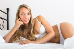 Woman wearing underwear posing on bed Stock Image