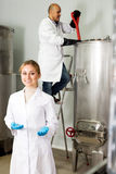 Woman wearing uniform standing among brewery Stock Photos