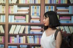 Woman Wearing V-neck Sleeveless Top Near Bookshelf royalty free stock image