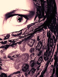 Woman Wearing Veil in Fear. A dramatic abstract portrait of a woman's eye peeking from behind a veil. It is difficult to know whether she is in fear, anger or Royalty Free Stock Photo